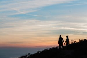 Alex and Jane hold hands as they walk through the hills of Marin Headlands with the sunsetting in the back.