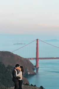 Jane and Alex kiss on a hill overlooking Golden Gate Bridge in the background.