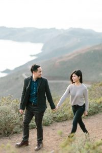 Alex holds Jane's hand as they walk through the hills of Marin Headlands.