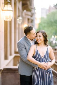 A couple in New York's Upper East Side for engagement photos with brownstone houses