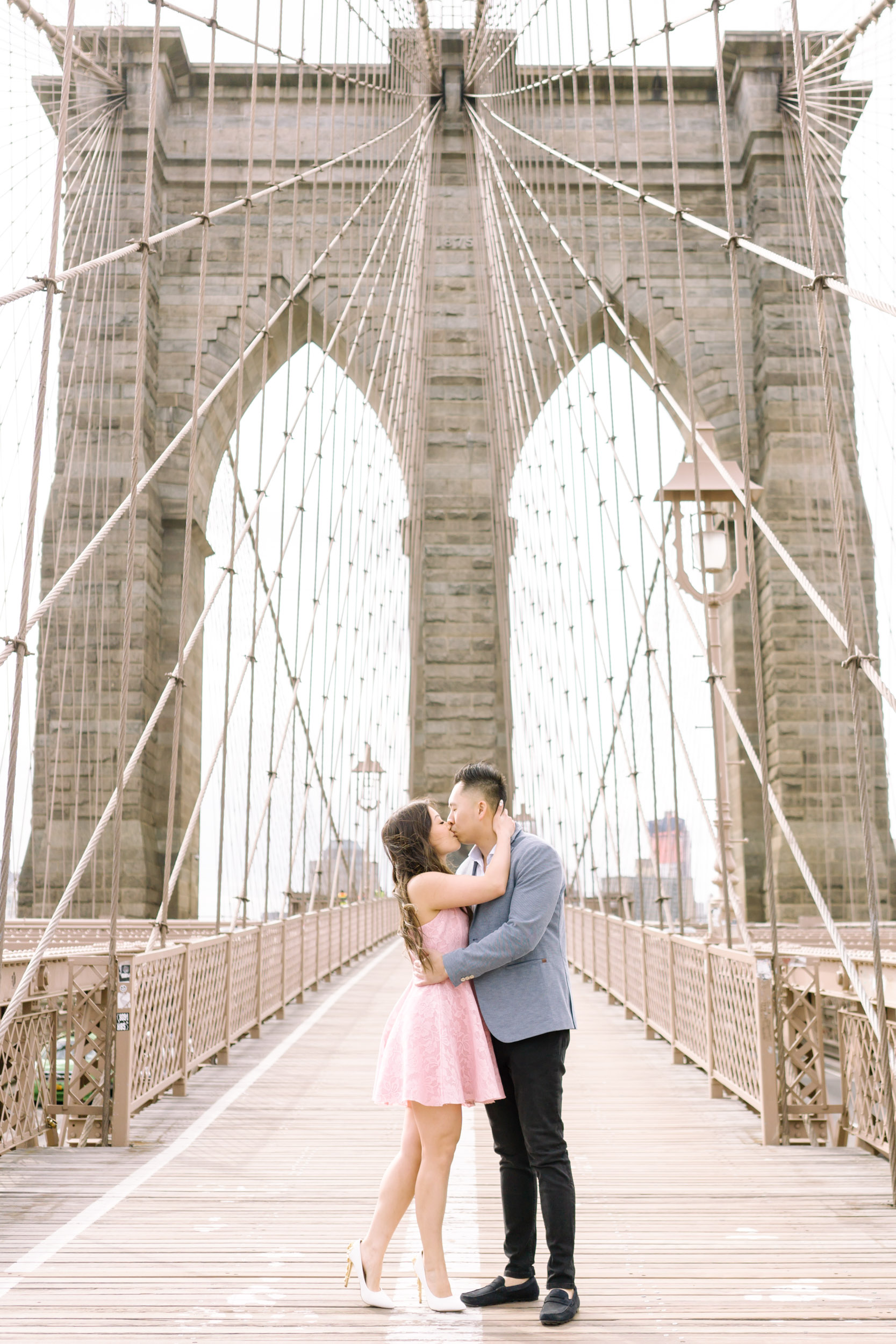 A couple at the Brooklyn Bridge in New York City for their engagement photos